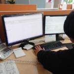 男性が電話を取りながらパソコン操作をしている画像
